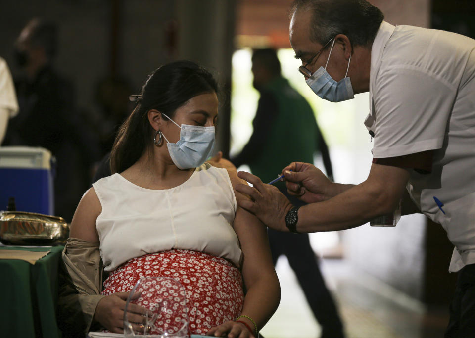 A pregnant woman gets a Pfizer vaccine shot for COVID-19 at a library converted into a vaccination center in Mexico City, Thursday, May 13, 2021. (AP Photo/Fernando Llano)