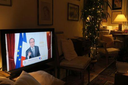 French President Francois Hollande, seen on a television screen in Asnieres, France, gestures as he gives his traditional New Year speech in a pre-recorded presentation at the Elysee Palace in Pari