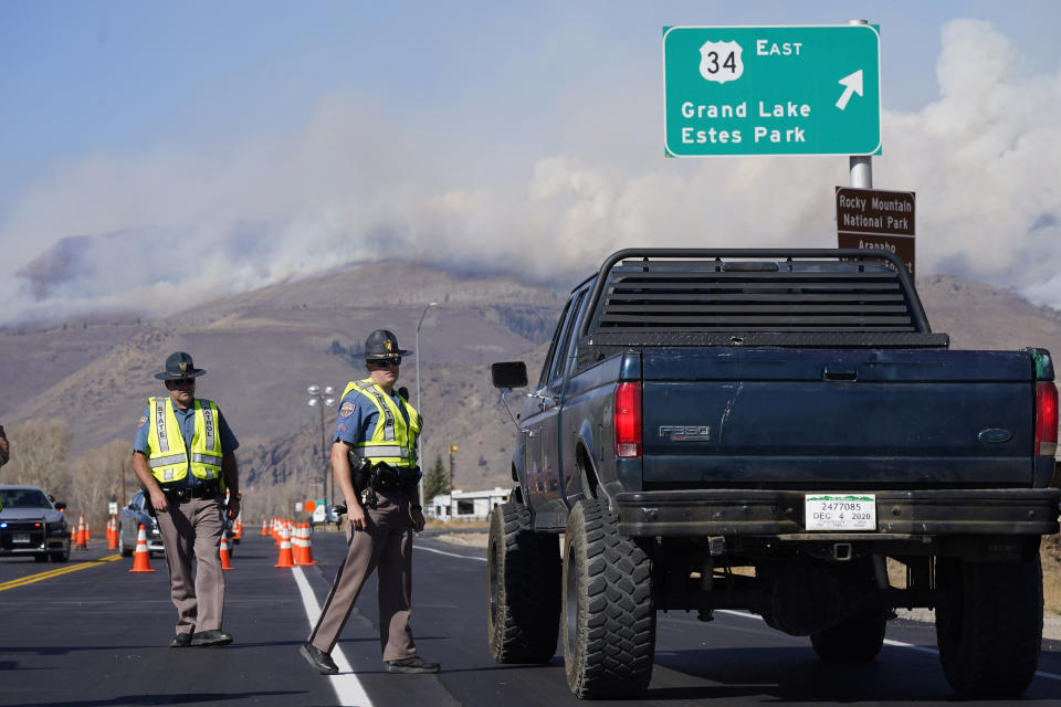 As smoke rises from mountain ridges in the background, Colorado State Patrol troopers stop a motorist on Highway 34 as a wildfire burns Thursday, Oct. 22, 2020, near Granby, Colo. (AP Photo/David Zalubowski)