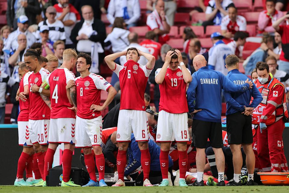 TOPSHOT - Denmark's players react as paramedics attend to Denmark's midfielder Christian Eriksen after he collapsed on the pitch during the UEFA EURO 2020 Group B football match between Denmark and Finland at the Parken Stadium in Copenhagen on June 12, 2021. (Photo by Friedemann Vogel / POOL / AFP) (Photo by FRIEDEMANN VOGEL/POOL/AFP via Getty Images)