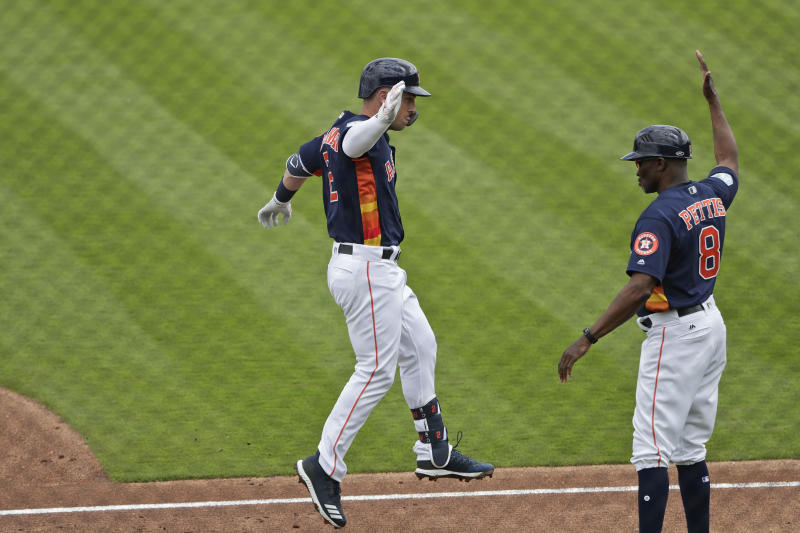Houston Astros' Alex Bregman (2) high-fives third base coach Gary Pettis (8) as he rounds third base after hitting a home run in the first inning during an exhibition spring training baseball game against the Miami Marlins, Thursday, March 14, 2019, in West Palm Beach Fla. (AP Photo/Brynn Anderson)