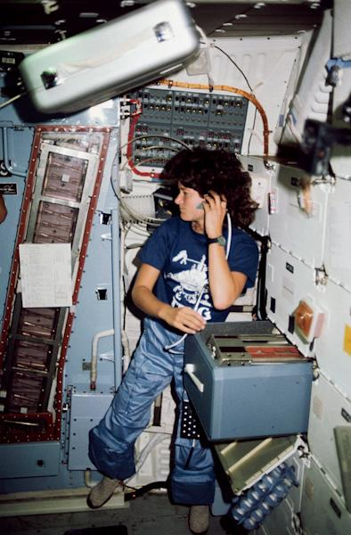 Astronaut Sally K. Ride, STS-7 mission specialist, communicates with ground controllers from the mid deck of the Earth-orbiting Space Shuttle Challenger. This image was taken in June 1983.
