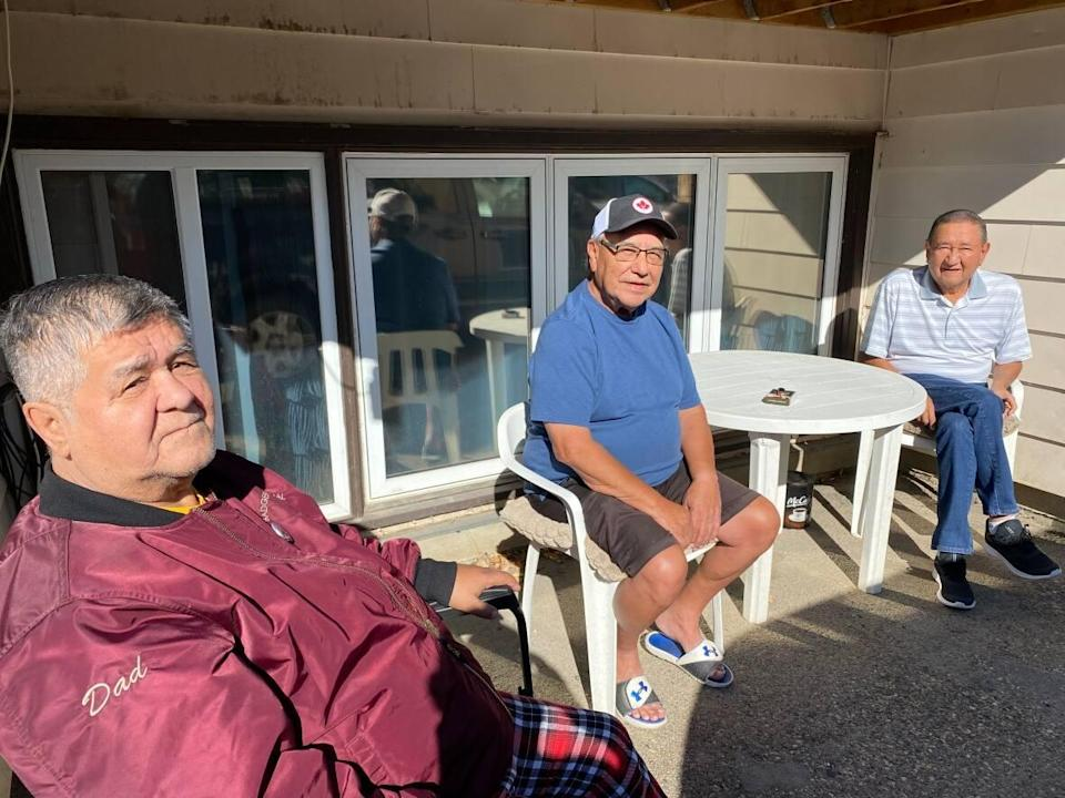 Residential school survivors Frank Badger, left, Rick Daniels, centre, and George Cameron, right, visit on the back patio of their Saskatoon apartment building. They say they're frustrated to learn Canada's first Indigenous justice minister, sworn in days earlier in November 2015, wasn't consulted before a key court document affecting survivors was filed in court. (Jason Warick/CBC - image credit)