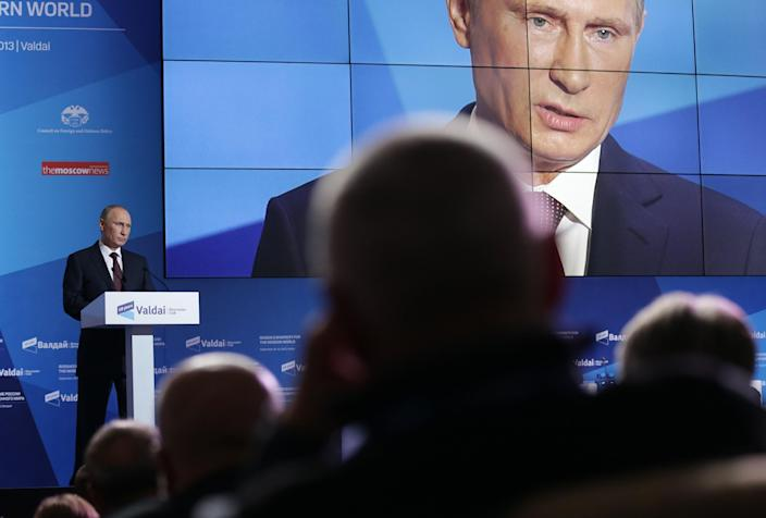 Russian President Vladimir Putin, left, speaks during the final plenary meeting of the Valdai International Discussion Club in the Novgorod Region, on the banks of Lake Valdai, Russia, Thursday, Sept. 19, 2013. (AP Photo/Maxim Shipenkov, pool)