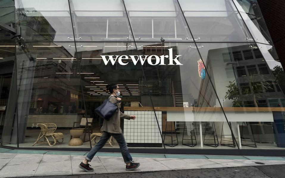 A pedestrian wearing a face mask walks past a WeWork co-working space - Tomohiro Ohsumi/Getty Images AsiaPac