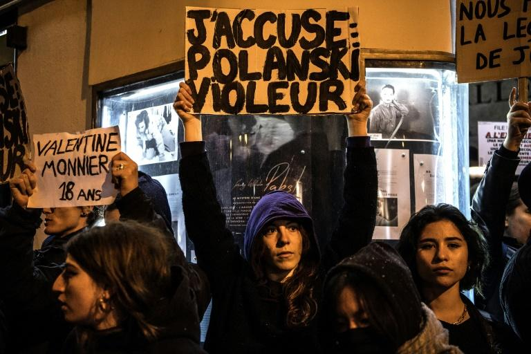"""A demonstrator holds a banner reading """"I accuse: Polanski Rapist"""" during a protest against the French-Polish film director's new movie outside a cinema in Paris this week"""