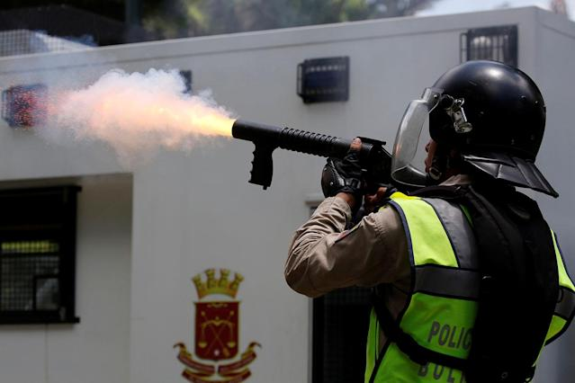 <p>A riot police officer fires tear gas at opposition supporters during a protest against President Nicolas Maduro in Caracas, Venezuela May 4, 2017. (Carlos Garcia Rawlins/Reuters) </p>