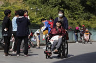 A woman wearing a face mask pushes an elderly man on a wheelchair passes by residents play with their children near a commercial office building in Beijing on Monday, May 10, 2021. China's population growth is falling closer to zero as fewer couples have children, the government announced Tuesday, adding to strains on an aging society with a shrinking workforce. (AP Photo/Andy Wong)
