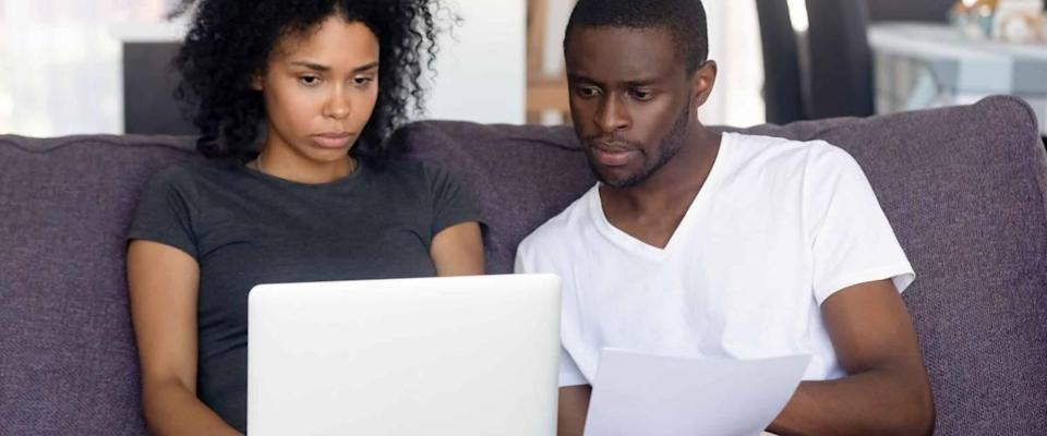 A worried black couple feel confused when they read the bad news from a letter received by the bank regarding the high costs of health insurance.