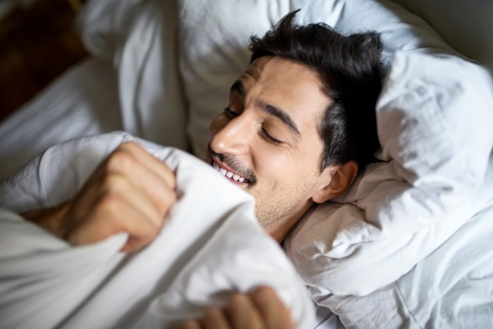 Smiling young man sleeping comfortably in bed at home