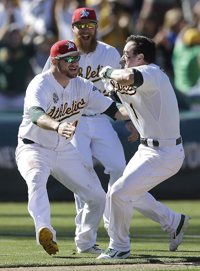 Oakland Athletics' Nick Punto, right, celebrates with Stephen Vogt, left, and Sean Doolittle after getting the game-winning hit in the 12th inning of a baseball game against the Toronto Blue Jays, Friday, July 4, 2014, in Oakland, Calif. (AP Photo/Ben Margot)
