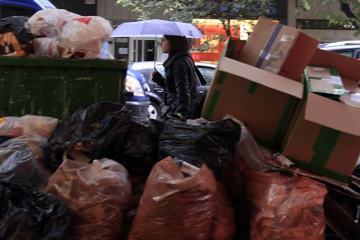 A woman passes a pile of garbage during on-going mobilizations by municipal workers in the northern Greek port city of Thessaloniki.