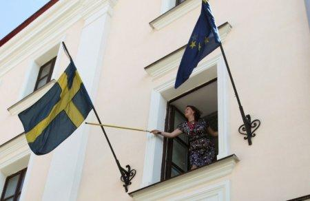 FILE PHOTO: An employee rearranges the national flag of Sweden at the Swedish embassy in Minsk August 8, 2012. REUTERS/Vasily Fedosenko/File Photo