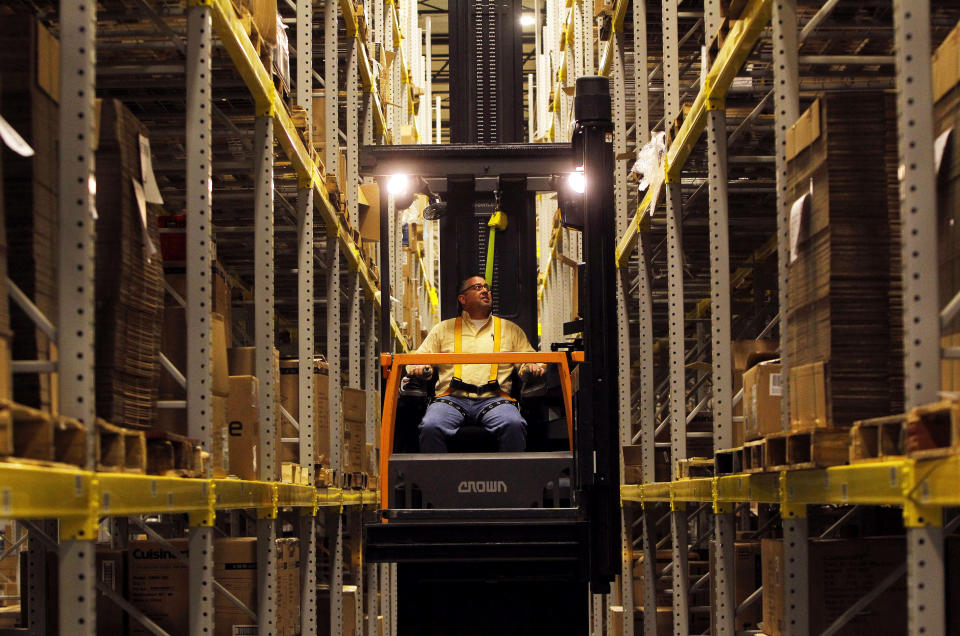 An associate at the Macy's-Bloomingdale's fulfillment center works down an aisle of packing boxes in Martinsburg, West Virginia December 6, 2012. REUTERS/Gary Cameron (UNITED STATES - Tags: BUSINESS)