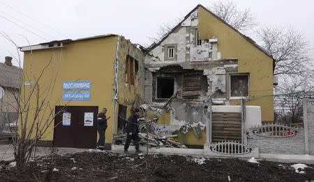 People walk past a house damaged by recent shelling in Mariupol