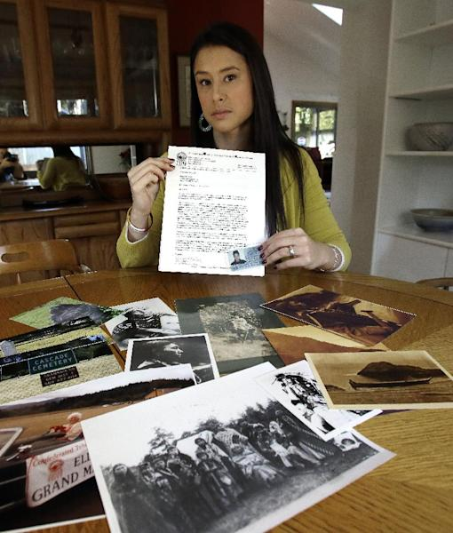 Mia Prickett sits at a table with a collection of family photos and holds her Confederated Tribe of Grande Ronde enrollment card along with a recent notice of potential potential disenrollment from the tribe in Portland, Ore., Thursday, Jan. 16, 2014. Prickett's ancestor Tumulth, a leader of the Cascade Indians along the Columbia River, was one of the chiefs who signed an 1855 treaty that helped establish the Confederated Tribes of the Grand Ronde in Oregon. But the Grand Ronde now wants to disenroll Prickett and 79 relatives because they no longer satisfy new enrollment requirements. (AP Photo/Don Ryan)