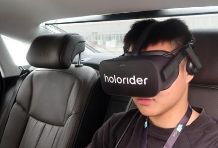 Staff member wears Holoride VR goggles inside an Audi vehicle during a demonstration at the CES Asia exhibition in Shanghai
