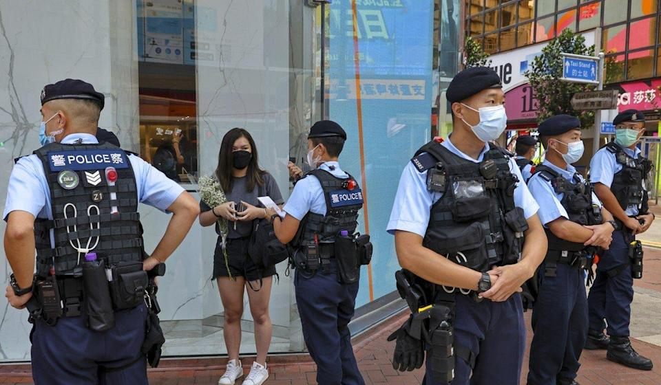 Police stop a woman carrying flowers near the scene of an attack in which a police officer was stabbed and the assailant committed suicide in Causeway Bay. Photo: Dickson Lee