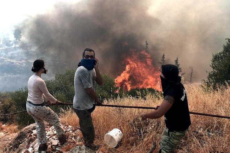 People stand in front of a fire in Athens on July 17, 2015. Greece appealed for EU help to battle wildfires raging on the outskirts of Athens and in the southern Peloponnese region that forced the evacuation of several villages