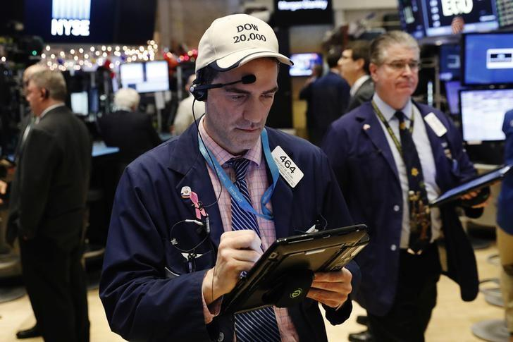 A trader wears a hat referencing the proximity of Dow Jones Industrial Average to 20,000 as he works on floor of the New York Stock Exchange (NYSE) shortly before the close of trading in New York
