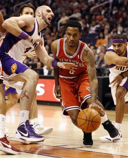 Milwaukee Bucks guard Brandon Jenning, center, drives between Phoenix Suns center Marcin Gortat, left, of Poland, and forward Jared Dudley, right, on his way to the basket in the first quarter of an NBA basketball game, Sunday, Jan. 8, 2012, in Phoenix. (AP Photo/Paul Connors)