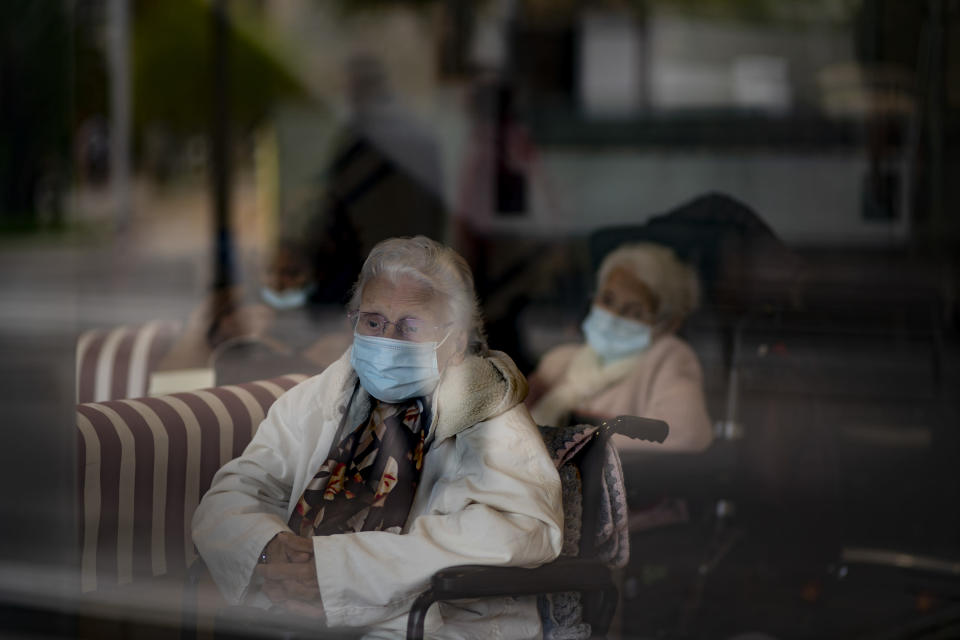 Residents look at the street through a window at the Icaria nursing home in Barcelona, Spain, Nov. 25, 2020. The image was part of a series by Associated Press photographer Emilio Morenatti that won the 2021 Pulitzer Prize for feature photography. (AP Photo/Emilio Morenatti)