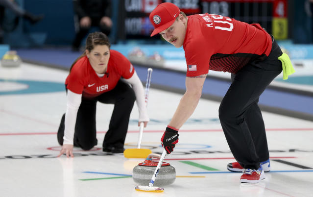 United States' Matt Hamilton sweeps the ice as his teammate and sister Becca watches, during a mixed double curling match at the 2018 Winter Olympics. (AP)