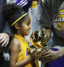 In this June 14, 2009, photo, Los Angles Lakers guard Kobe Bryant's daughter Gianna holds her father's MVP trophy after the Lakers 99-86 defeat of the Orlando Magic in Game 5 of the NBA Finals at Amway Arena in Orlando. Bryant, his 13-year-old daughter Gianna and several others are dead after their helicopter went down in Southern California on Sunday, Jan. 26, 2020. (Stephen M. Dowell/Orlando Sentinel via AP)