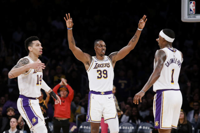 Los Angeles Lakers' Danny Green (14) celebrates with teammates Dwight Howard (39) and Kentavious Caldwell-Pope (1) after making a 3-pointer during the first half of an NBA basketball game, Sunday, Dec. 8, 2019, in Los Angeles. (AP Photo/Ringo H.W. Chiu)