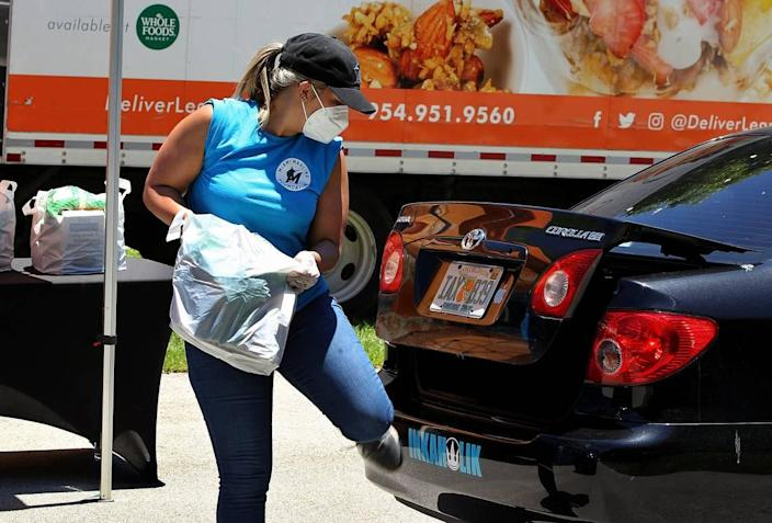 Sarah Garcia, with the Miami Marlins, places a bag of goods in a car's trunk at a drive-thru only food distribution next to Marlins Park hosted by DeliverLean in partnership with the Miami Marlins Foundation to provide non-perishable items and/or a fresh meal to anyone in need due to the COVID-19 pandemic, on Tuesday, May 05, 2020.