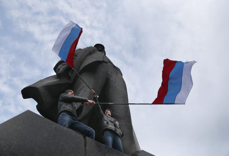 "Men wave Russian national flags underneath a statue of Soviet revolutionary leader Vladimir Lenin during a pro Russian rally at a central square in Donetsk, eastern Ukraine, Sunday, March 9, 2014. Following an extraordinary meeting of the Ukrainian government, Prime Minister Arseniy Yatsenyuk announced he would be flying later this week to the United States for high-level talks on ""resolution of the situation in Ukraine,"" the Interfax news agency reported Sunday. (AP Photo/Sergei Grits)"