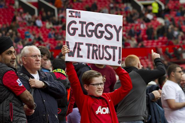 A young Manchester United supporter holds a placard in support of of interim manager Ryan Giggs before the team's English Premier League soccer match against Norwich City at Old Trafford Stadium, Manchester, England, Saturday April 26, 2014. (AP Photo/Jon Super)