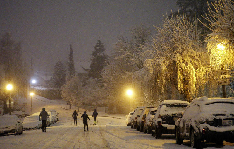 Cross country skiers travel on a street in Tacoma, Wash., the night of Friday, Feb. 8, 2019, during a storm that dropped inches of snow throughout the region and left trees and cars coated in snow and ice. (AP Photo/Ted S. Warren)