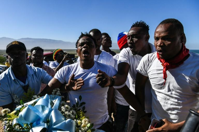 Protestors shout anti-government slogans outside a mass graveyard during the commemorative ceremonies of Haiti's 10th earthquake anniversary on the outskirts of Port-au-Prince, on January 12, 2020
