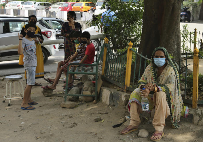 Indians wearing face masks wait to consult doctors outside a COVID-19 screening facility at a government run hospital in Jammu, Saturday, June 27, 2020. India is the fourth hardest-hit country by the pandemic in the world after the U.S., Russia and Brazil. (AP Photo/Channi Anand)