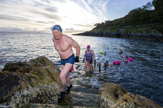 Open water swimmers take an early morning dip at Brompton in Bangor, County Down, after restrictions in Northern Ireland eased
