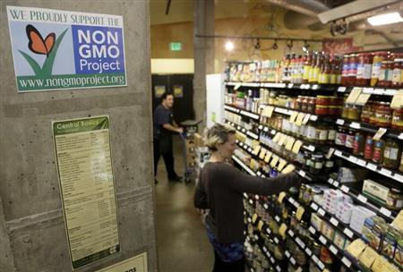 Employees stock shelves near a sign supporting non genetically modified organisms (GMO) at the Central Co-op in Seattle, Washington