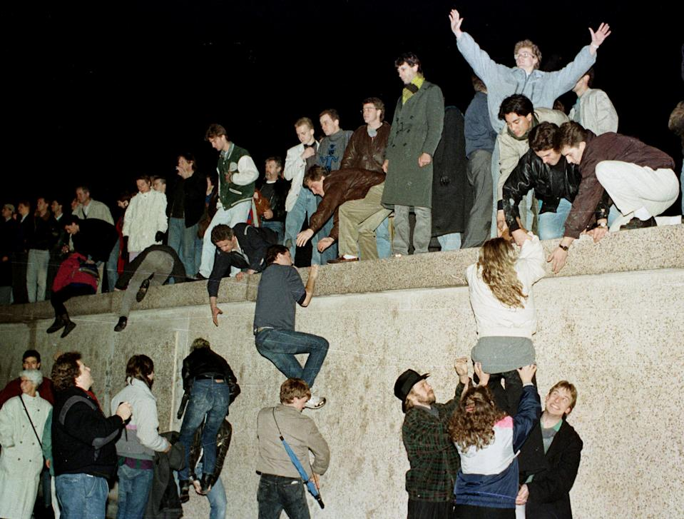 People climb the Berlin wall at the Brandenburg Gate as they celebrate the opening of the East German border Nov. 9, 1989. (Photo: Herbert Knosowski/Reuters)