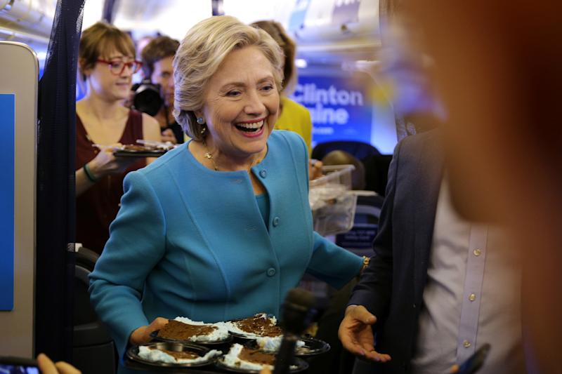 Clinton brings birthday cake to members of the media inside her campaign plane en route to New York on October 26, 2016. (Carlos Barria / Reuters)