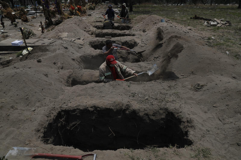 Melvin Sanaurio, front, a gravedigger for 15 years, works at the San Lorenzo Tezonco Iztapalapa cemetery as it makes space for more burials in a section for COVID-19 victims, in the Iztapalapa neighborhood of Mexico City, Tuesday, June 2, 2020. Mexico is passing through the pandemic's most critical moment with a dramatically increasing number of confirmed and suspected infections. (AP Photo/Marco Ugarte)