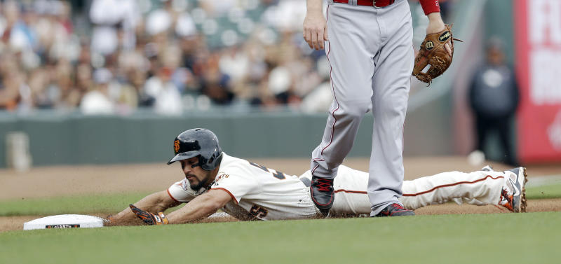 San Francisco Giants' Andres Torres slides safely into third base a after a single from Marco Scutaro during the first inning of the first game of a baseball doubleheader against the Cincinnati Reds on Tuesday, July 23, 2013, in San Francisco. (AP Photo/Marcio Jose Sanchez)