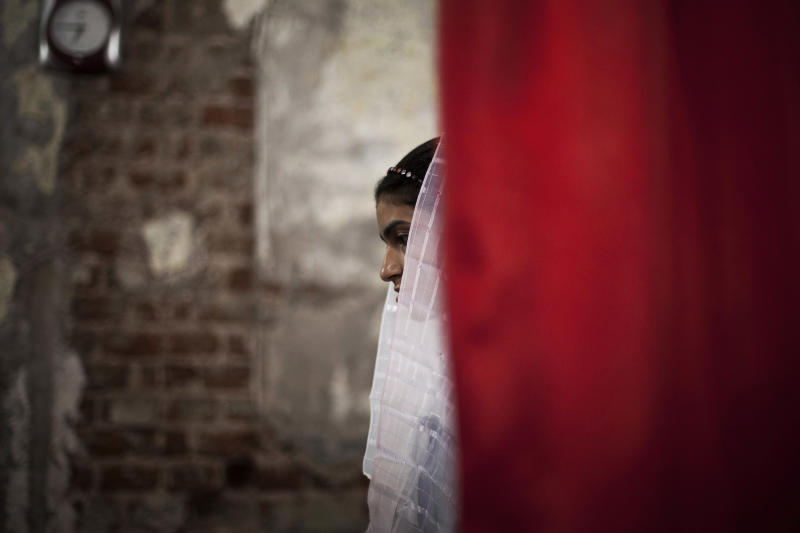In this Thursday, Oct. 2, 2013 photo, an Egyptian Coptic woman prays at a church burnt by radical Islamists on Aug. 14 in the town of Abanoub, some 400 kilometers (250 miles) south of Cairo. In a show of resilience, some have held Masses and weddings in churches that have been left blackened shells without doors or windows, with only a makeshift altar. Still, priests say, some regular worshippers have stayed away, too hurt to return and see the condition of the churches where they lived out milestones like weddings, baptisms and funerals. (AP Photo/Manu Brabo)