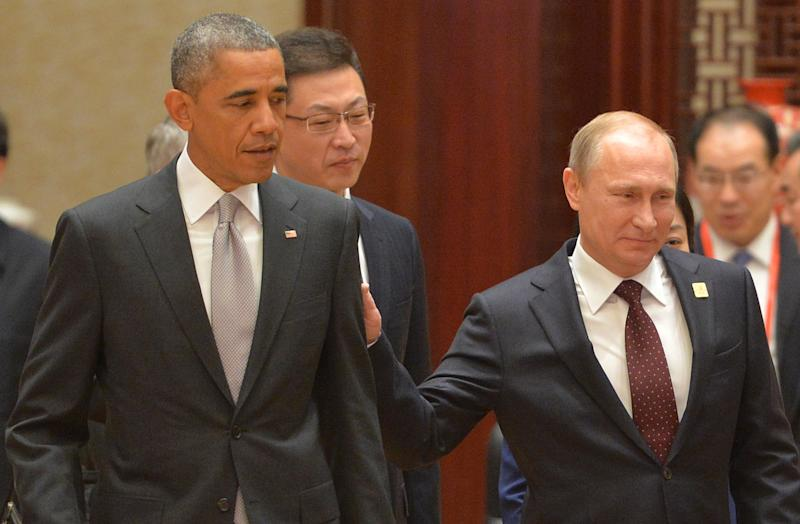 Russian President Vladimir Putin (R) touches US President Barack Obama as they arrive at the Asia-Pacific Economic Cooperation Summit plenary session in Beijing on November 11, 2014