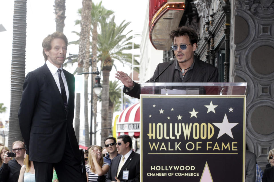 Actor Johnny Depp (R) speaks in tribute to film and television producer Jerry Bruckheimer during ceremonies honoring Bruckheimer with a star on the Hollywood Walk of Fame in Hollywood June 24, 2013. REUTERS/Fred Prouser (UNITED STATES - Tags: ENTERTAINMENT)