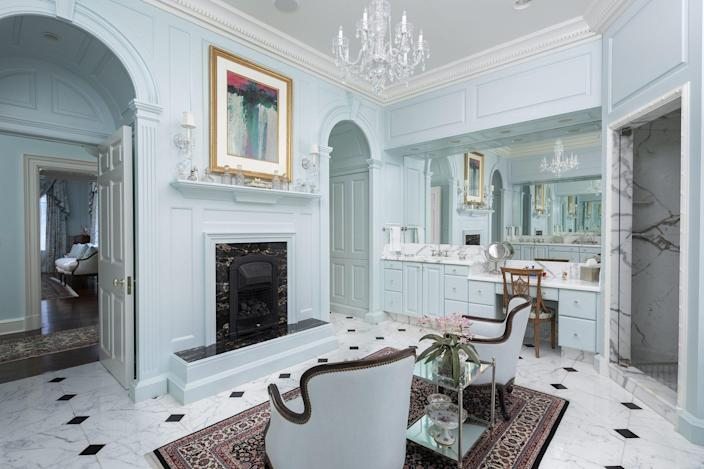 Have you ever seen such a bathroom? Statuary marble, dual vanities, an English style gas fireplace, and a second crystal chandelier are just a few of the standout features here, along with a separate tub and shower.