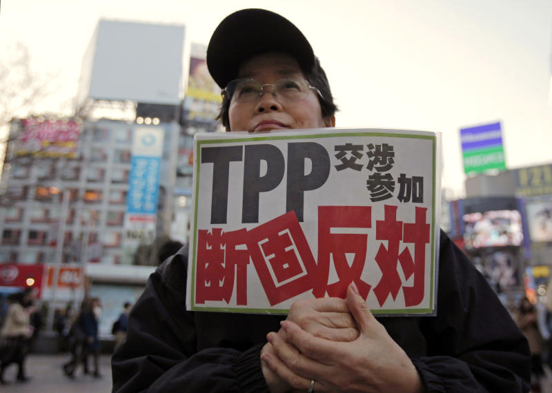 "In this Thursday, March 14, 2013 photo, a protester holds a sign reading ""We oppose Japan to join the TPP negotiation talks"" during a rally against the Trans-Pacific Partnership in Tokyo. Prime Minister Shinzo Abe is set to announce Japan will join talks on a Pacific trade pact that would oblige the country to undertake major reforms, especially in farming. The expected announcement later Friday confirming plans to seek participation in the U.S.-led TPP is raising protests from farmers opposed to opening protected home markets to foreign competition. (AP Photo/Shuji Kajiyama)"