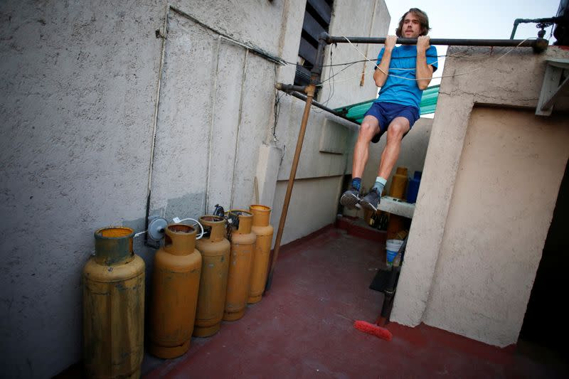 A man exercises on a roof as the spread of the coronavirus disease (COVID-19) continues in Mexico City