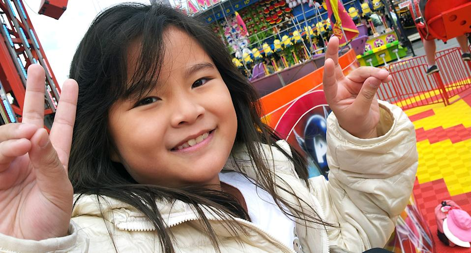 Eight-year-old Malaysian national Adelene Leong smiles and poses for a photo while at a fair.