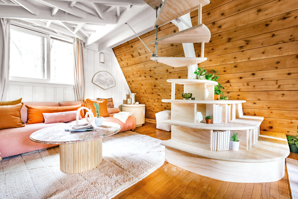 living room with wood and white walls, blush sofa