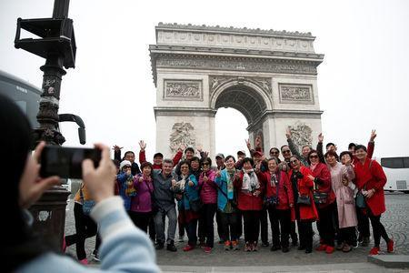 """Chinese tourists pose for photos in front of the Arc de Triomphe on the Champs-Elysees avenue during the Act XIX (the 19th consecutive national protest on a Saturday) of the """"yellow vests"""" movement in Paris, France, March 23, 2019. REUTERS/Benoit Tessier"""